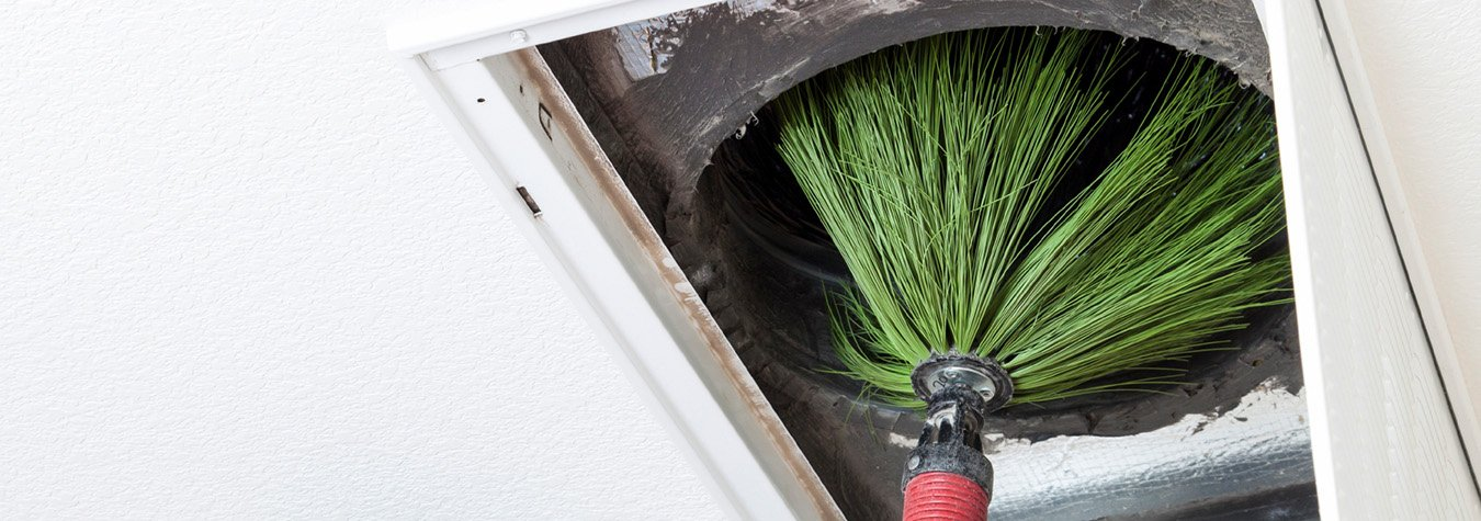 using brush to clean air ductwork